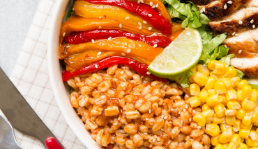 Buddha bowl mexicain orge mondé, maïs, poulet poivrons vue de dessus